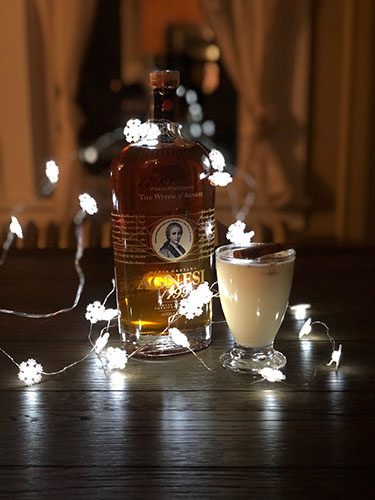 A cream colored Tom & Jerry cocktail in a glass garnished with a cinnamon stick next to a bottle of Agnesi brandy with a string of lit snowflake shaped Christmas lights.