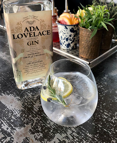 A bottle of Ada Lovelace Gin next to a glass filled with a Gin & Tonic cocktail that is garnished with a lemon slice and rosemary sprig.