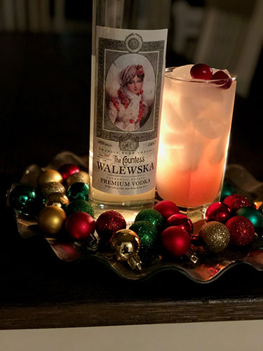 Countess Walewska vodka bottle next to a cocktail in glass that is garnished with cranberries, surrounded by Christmas bulbs.