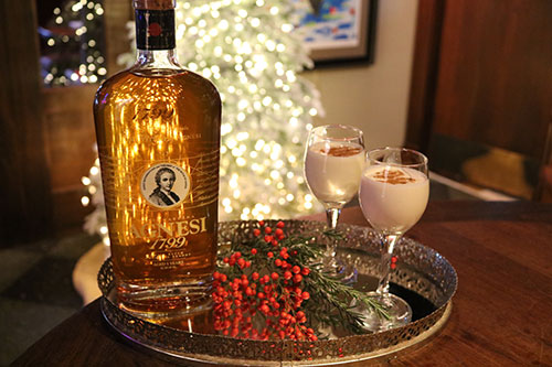 Two glasses of Coquito and a bottle of Agnesi brandy on a tray with an illuminated Christmas tree in the background.