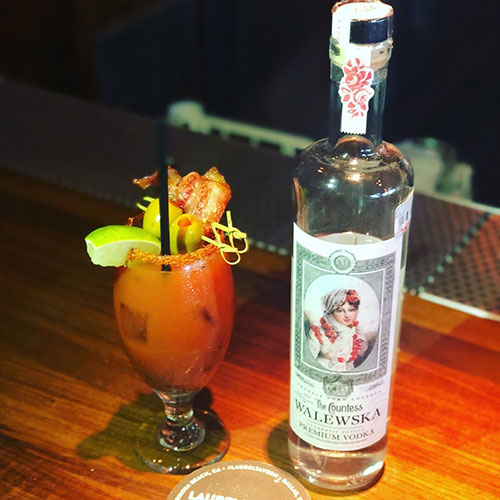 A heavily garnished Bloody Mary cocktail with a lime wedge, olives, and bacon, sitting next to a bottle of Countess Walewska Vodka on a wooden bartop.