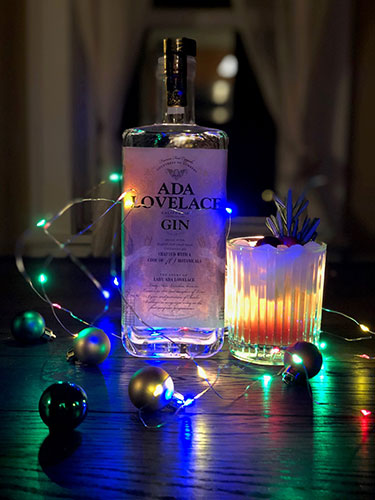 Cranberry Ginger Ale Fizz cocktasil in a glass garnished with a rosemary sprig next to a bottle of Ada Lovelace Gin, surounded by a string of colorful Christmas lights and bulbs.