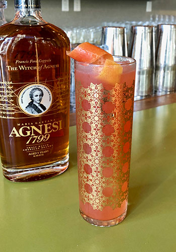 A bottle of Agnesi Brandy on a green bar top next to peach colored cocktail inside gold filagree decorated Collins glass garnished with a orange peel twist.