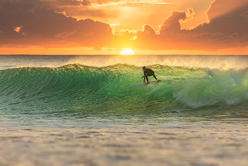 Surfer riding a wave at sunset.