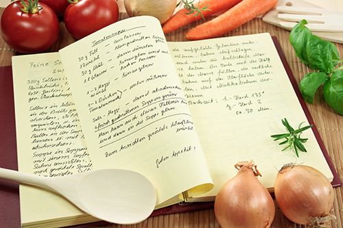 A handwritten cookbook opened surrounded by vegtables and on a butcherblock.