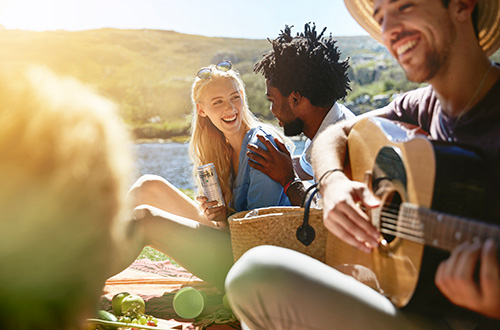 Man playing an acoustic guitar to a group of friends at a lakeside picnic.