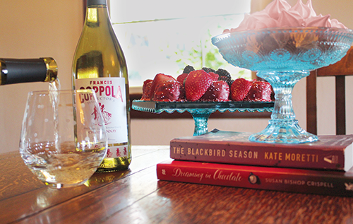 Bottle of Director's Chardonnay with a tray of strawberries and a bowl of meringues cookies.