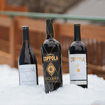 Bottles of Director's Pinot Noir, Diamond Collection Claret, and Director's Cabernet Sauvignon wine in the snow.