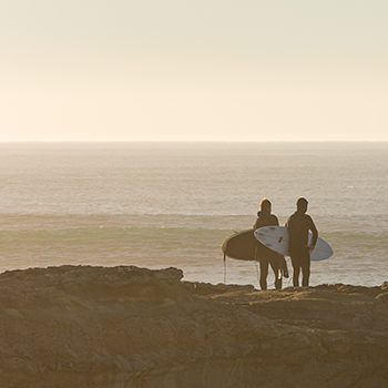 A pair of surfers standing on a cliff over the ocean.