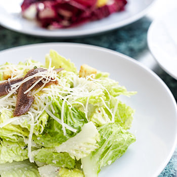 A plate of Caesar Salad on a green marble table top.