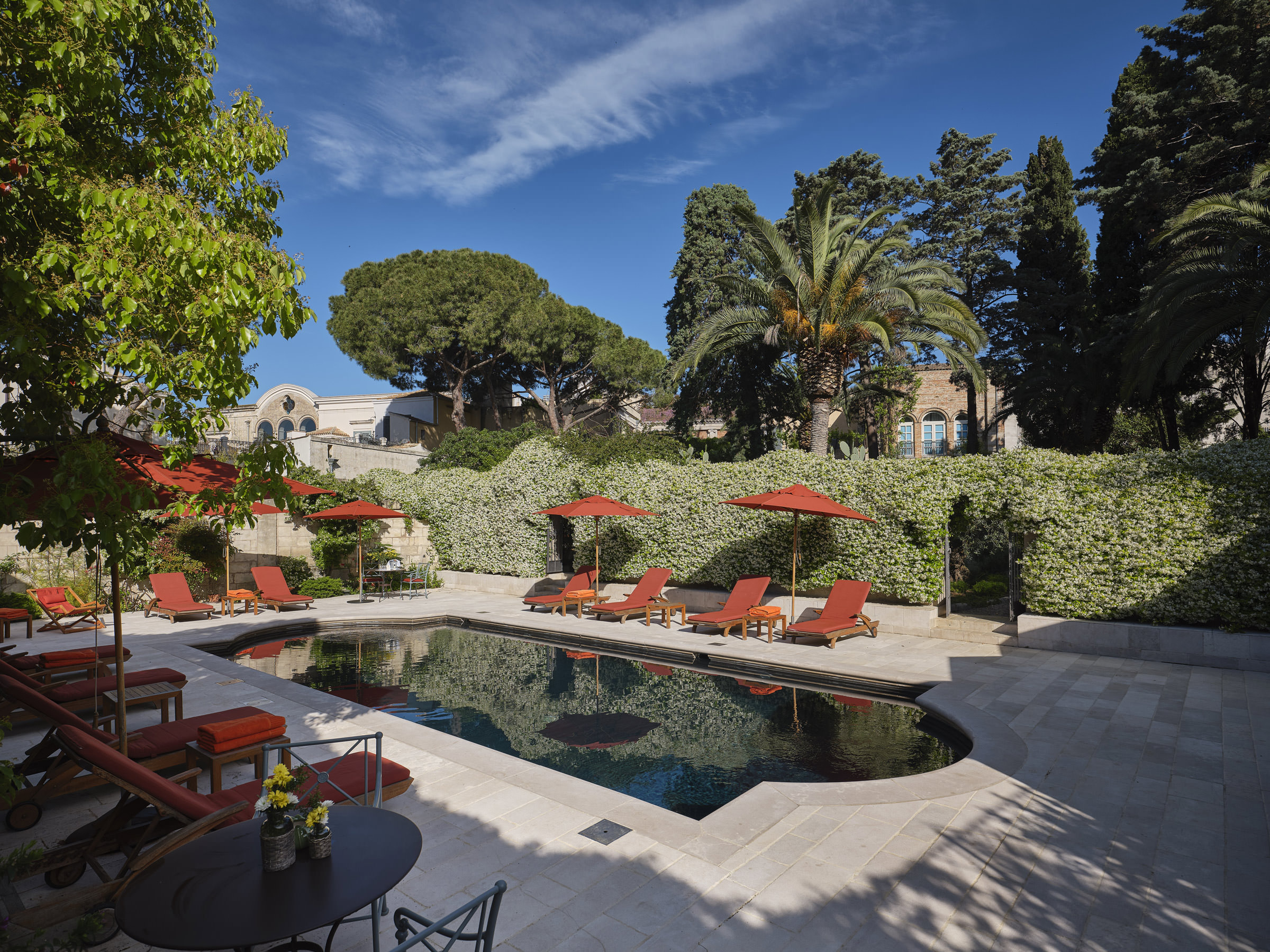 A pool with orange lounge chairs and an ivy covered wall.