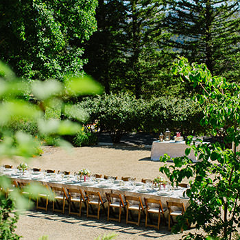 A long table set up for a wedding reception outside.