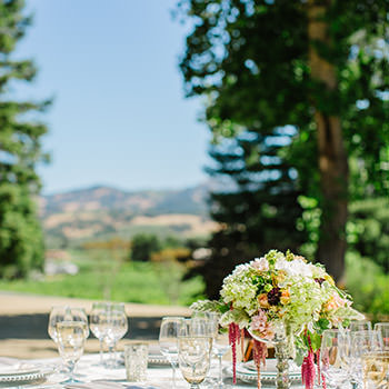 A table set up with glassware and floral centerpieces.