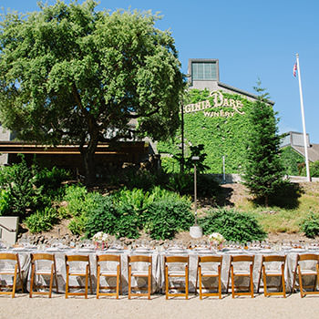 A wedding reception set up outside with the winery in the background.