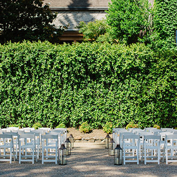 Chairs set up for wedding ceremony with a wall covered in ivy in the background.
